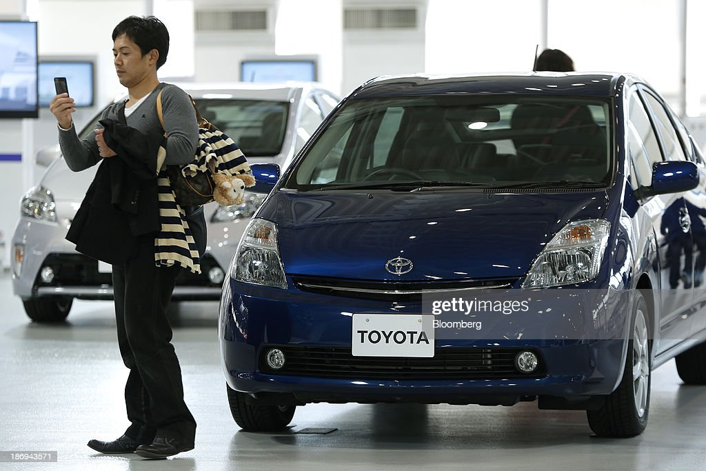 A visitor uses a mobile device next to a Toyota Motor Corp. second-generation Prius vehicle on display at the company's showroom in Tokyo, Japan, on Tuesday, Nov. 5, 2013. Toyota, the world's largest automaker, will probably deliver record semiannual profit when it reports earnings tomorrow, as the weaker yen bolsters the value of Japanese cars sold overseas. Photographer: Kiyoshi Ota/Bloomberg via Getty Images