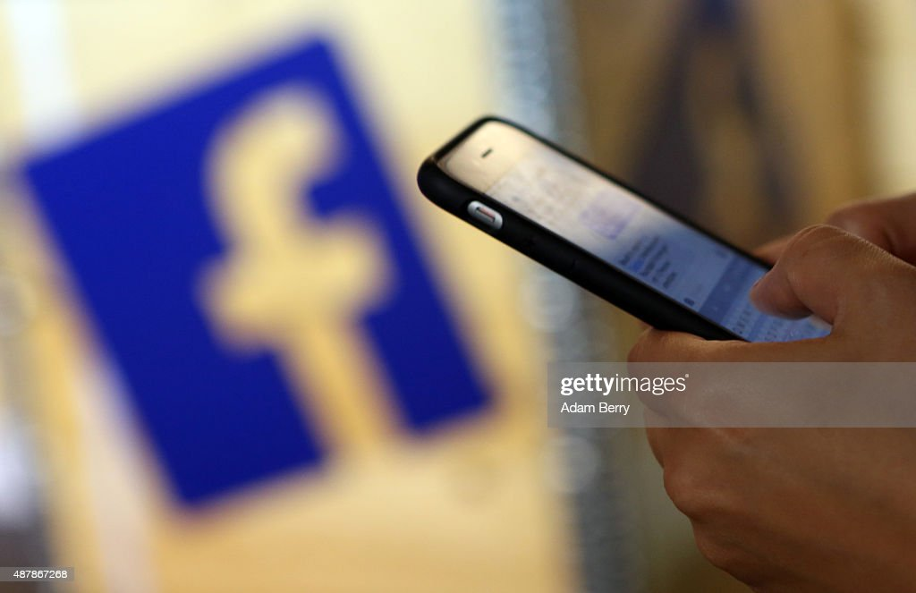 A visitor uses a mobile phone in front of the Facebook logo at the #CDUdigital conference on September 12 2015 in Berlin Germany The world's largest...
