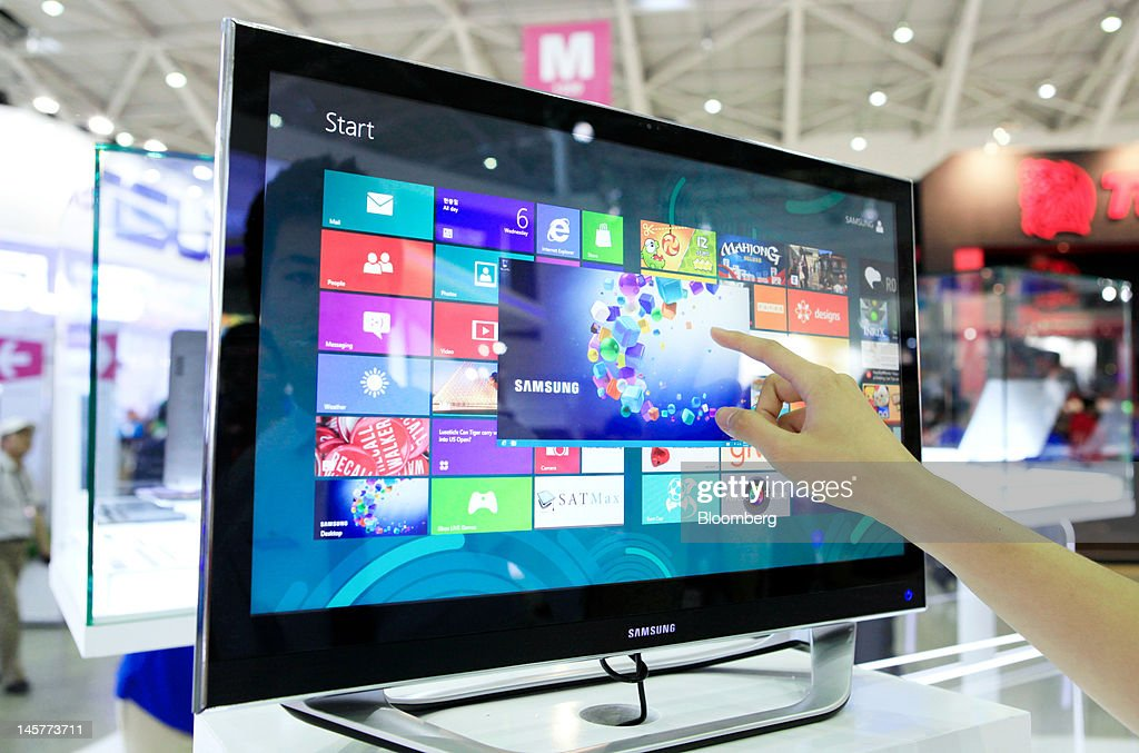 A visitor uses a Samsung Electronics Co. Series 7 computer at the Samsung booth at the Computex Taipei 2012 expo in Taipei, Taiwan, on Tuesday, June 5, 2012. Computex Taipei 2012 takes place from June 5 to June 9. Photographer: Ashley Pon/Bloomberg via Getty Images