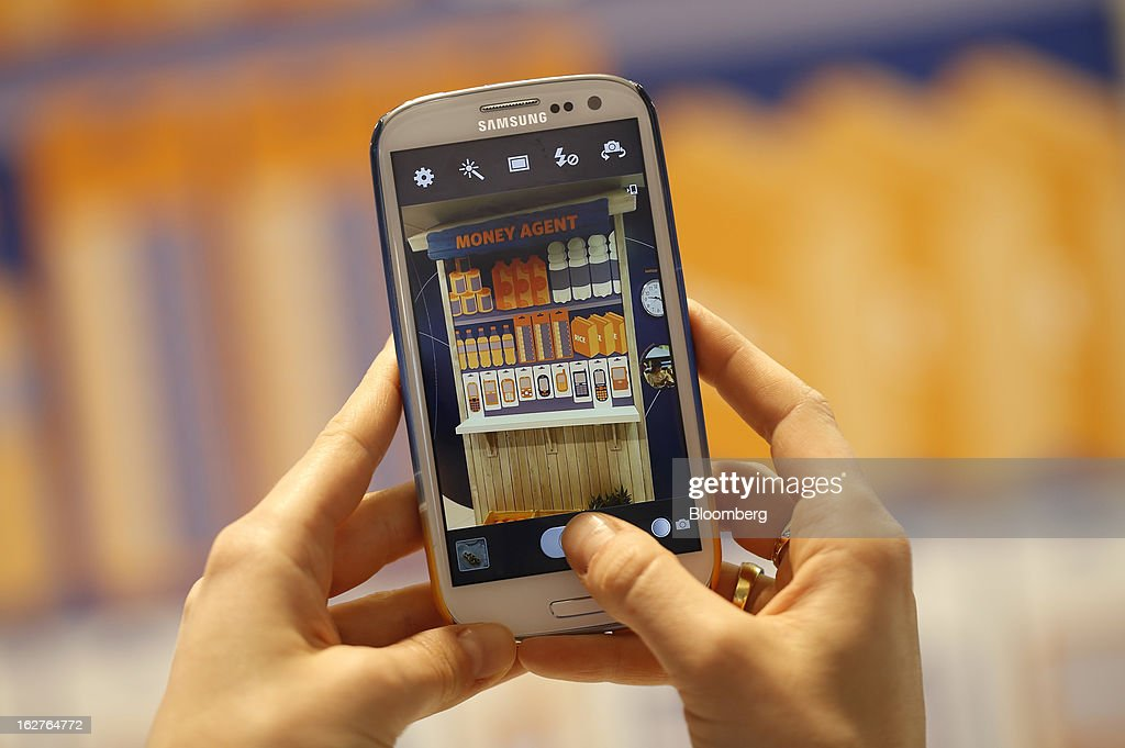 A visitor uses a Samsung Galaxy SIII smartphone to photograph an advertisement for contactless payment at the Mobile World Congress in Barcelona, Spain, on Tuesday, Feb. 26, 2013. The Mobile World Congress, where 1,500 exhibitors converge to discuss the future of wireless communication, is a global showcase for the mobile technology industry and runs from Feb. 25 through Feb. 28. Photographer: Simon Dawson/Bloomberg via Getty Images