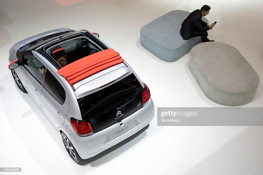 A visitor uses a smartphone as he sits near a Citroen C1 automobile produced by PSA Peugeot Citroen on day two of the 85th Geneva International Motor...