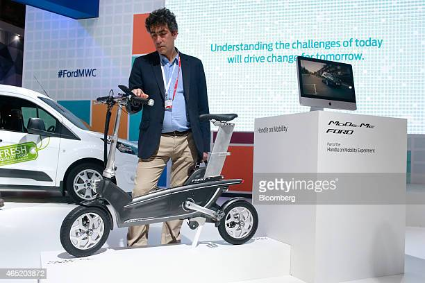 A visitor uses a smartphone navigation system on a Ford MoDeMe foldable ebike at the Ford Motor Co pavilion at the Mobile World Congress in Barcelona...
