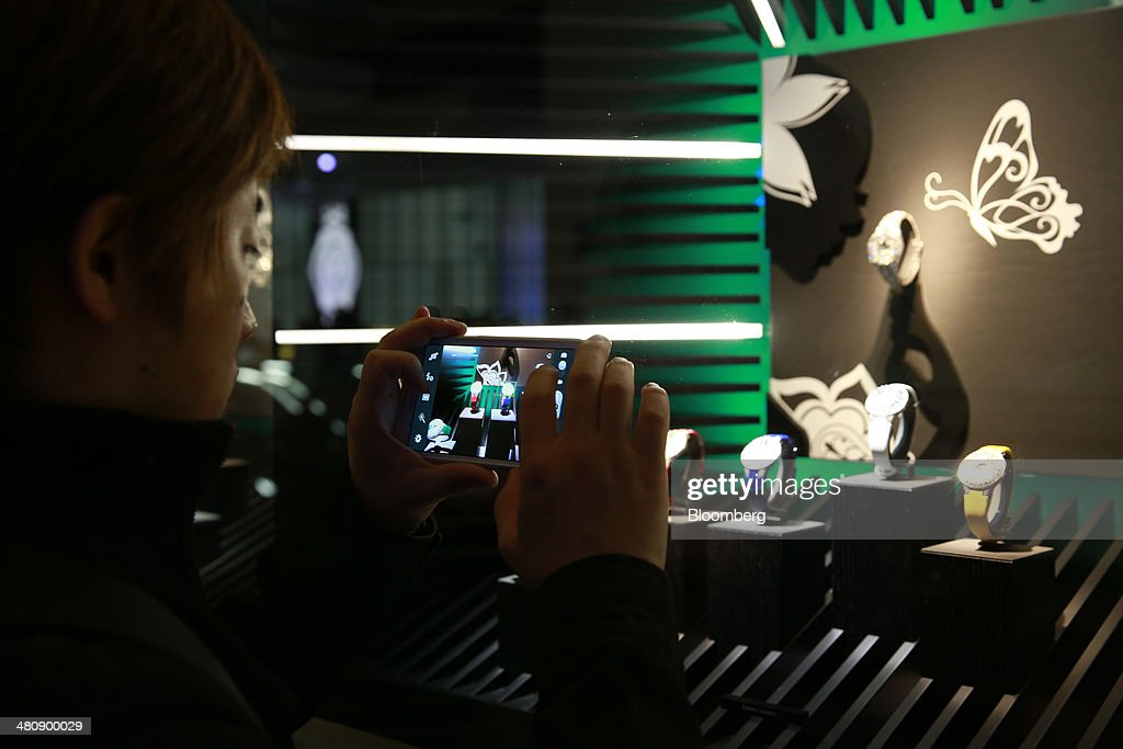 A visitor uses a smartphone to photograph a display of Graff Butterfly wristwatches, produced by Graff Diamonds Ltd., at the company's booth during the Baselworld luxury watch and jewelry fair in Basel, Switzerland, on Thursday, March 27, 2014. Over 1,400 companies from the watch, jewelry and gem industries will display their latest innovations and products to more than 120,000 visitors at this year's luxury show. Photographer: Gianluca Colla/Bloomberg via Getty Images