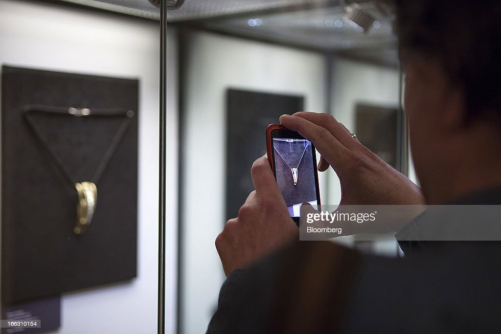 A visitor uses a smartphone to photograph an item in a display of luxury diamond art jewelry exhibited at the Kremlin Museum by OAO Alrosa in Moscow, Russia, on Thursday, April 11, 2013. OAO Alrosa may be valued at $9.4-10.8B when the Russian government looks to sell stake in the company in November, Vedomosti newspaper says, citing two unidentified bankers close to Goldman Sachs. Photographer: Alexander Zemlianichenko Jr./Bloomberg via Getty Images