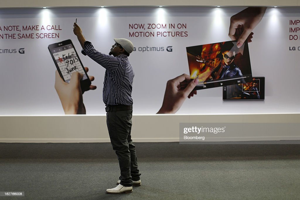 A visitor uses a smartphone to photograph himself in front of an advertisement for LG Optimus G smartphones at the Mobile World Congress in Barcelona, Spain, on Tuesday, Feb. 26, 2013. The Mobile World Congress, where 1,500 exhibitors converge to discuss the future of wireless communication, is a global showcase for the mobile technology industry and runs from Feb. 25 through Feb. 28. Photographer: Simon Dawson/Bloomberg via Getty Images