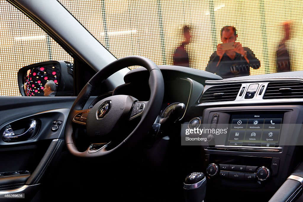 A visitor uses a smartphone to take a photograph of a Renault Kadjar automobile produced by Renault SA on day two of the 85th Geneva International...