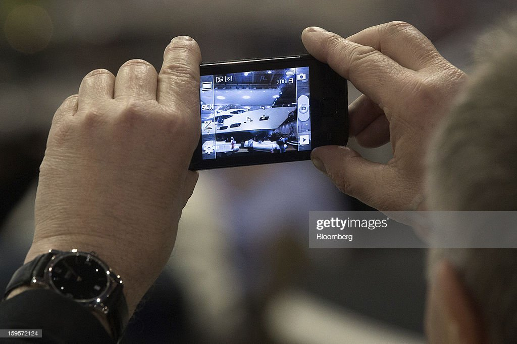 A visitor uses a smartphone to take a photograph of a Sunseeker International Ltd luxury yacht during the Tullet Prebon London Boat Show 2013 at the ExCeL center in London, U.K., on Wednesday, Jan. 16, 2013. The show, Europe's first in 2013, will showcase new sailing craft from dinghies to luxury yachts, and runs Jan. 12-20. Photographer: Simon Dawson/Bloomberg via Getty Images