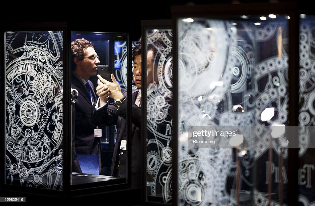 A visitor uses a smartphone to take a photograph of a wristwatch on display at the Piaget, a unit of Cie. Financiere Richemont SA, booth during the first day of the Salon International de la Haute Horlogerie (SIHH) watch fair in Geneva, Switzerland, on Monday, Jan. 21, 2013. The Swiss watch industry slowed in the second half of 2012 as sales of timepieces and jewelry in Hong Kong, the biggest market for Swiss watchmakers, declined in August and October. Photographer: Valentin Flauraud/Bloomberg via Getty Images
