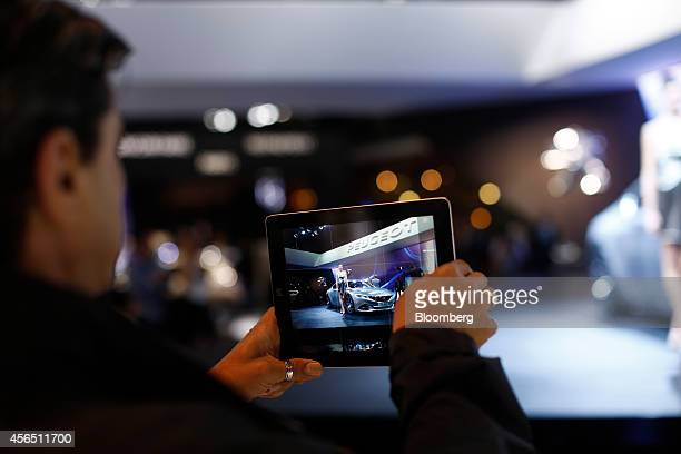 A visitor uses a tablet computer to photograph a Peugeot Exalt automobile at the Paris Motor Show in Paris France on Thursday Oct 2 2014 The show...