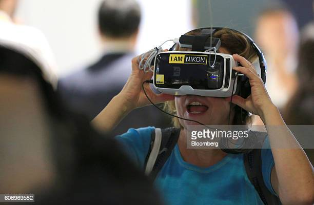 A visitor uses a virtual reality headset to view images shot on a Nikon KeyMission 360 digital camera manufactured by Nikon Inc during the Photokina...