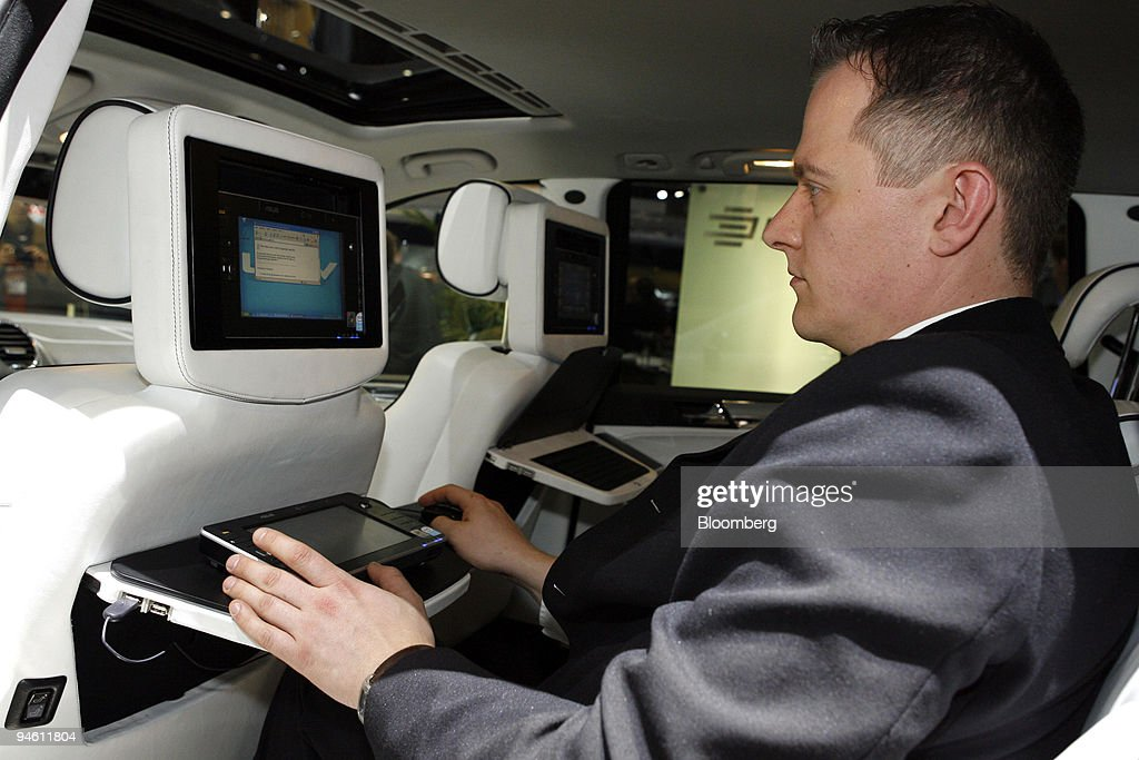 A visitor uses a Windows XP computer installed in the back of a headrest of an automobile on the first day of the media preview for the Geneva...