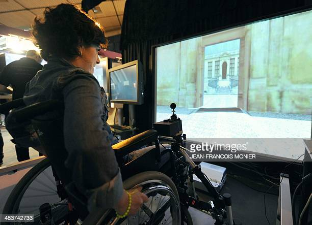 A visitor uses an electric wheel chair as she moves in a virtual world created with the 'AccesSim' software on April 9 at the 16th edition of the...