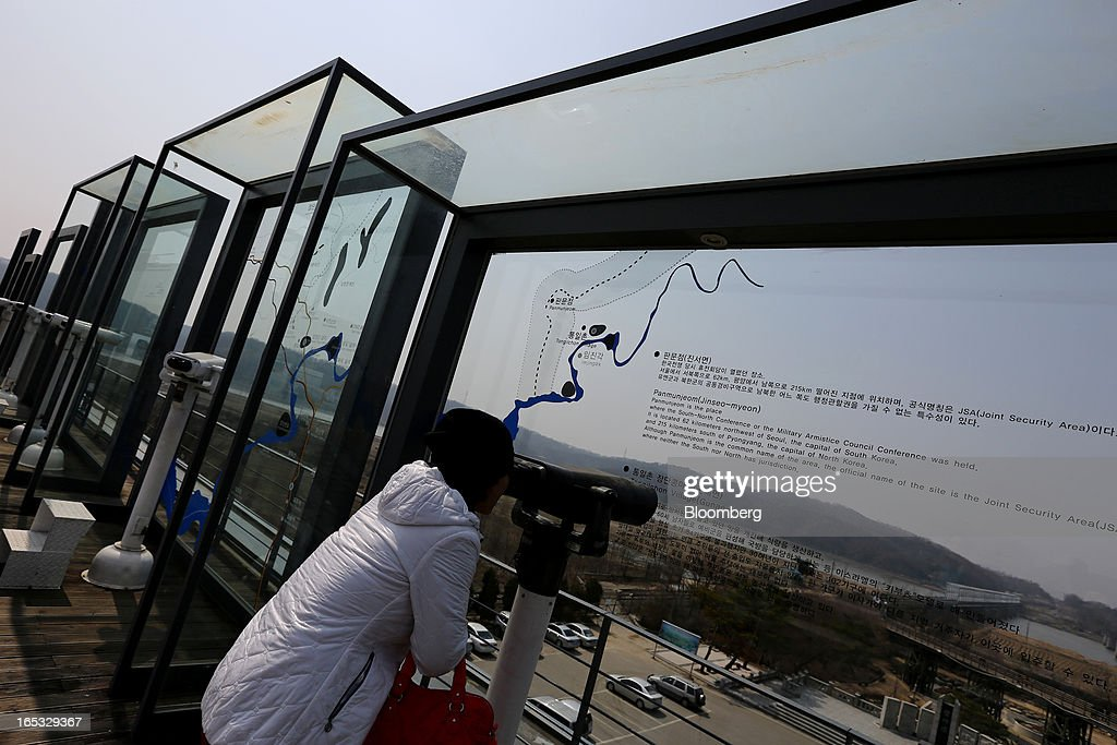 A visitor uses binoculars as she looks across to the north side of the border at the Imjingak pavilion near the demilitarized zone (DMZ) in Paju, South Korea, on Wednesday, April 3, 2013. North Korea prevented South Korean workers from entering a jointly run industrial park today, adding to tensions after saying it will restart a mothballed nuclear plant and threatening to attack its southern neighbor. Photographer: SeongJoon Cho/Bloomberg via Getty Images