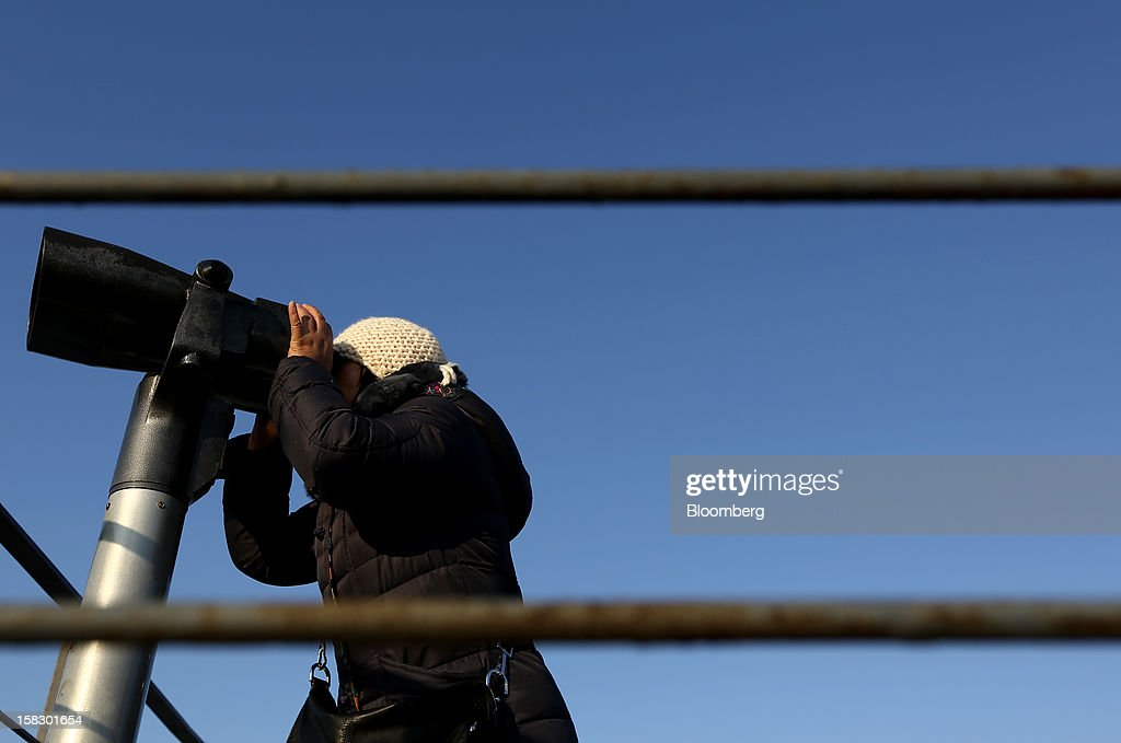 A visitor uses binoculars to look across to the north side of the border at the Imjingak pavilion near the demilitarized zone (DMZ) in Paju, South Korea, on Wednesday, Dec. 12, 2012. North Korea fired a rocket that placed a satellite into orbit, defying international sanctions and showcasing the nuclear-armed totalitarian regime's progress in ballistic missile technology. Photographer: SeongJoon Cho/Bloomberg via Getty Images