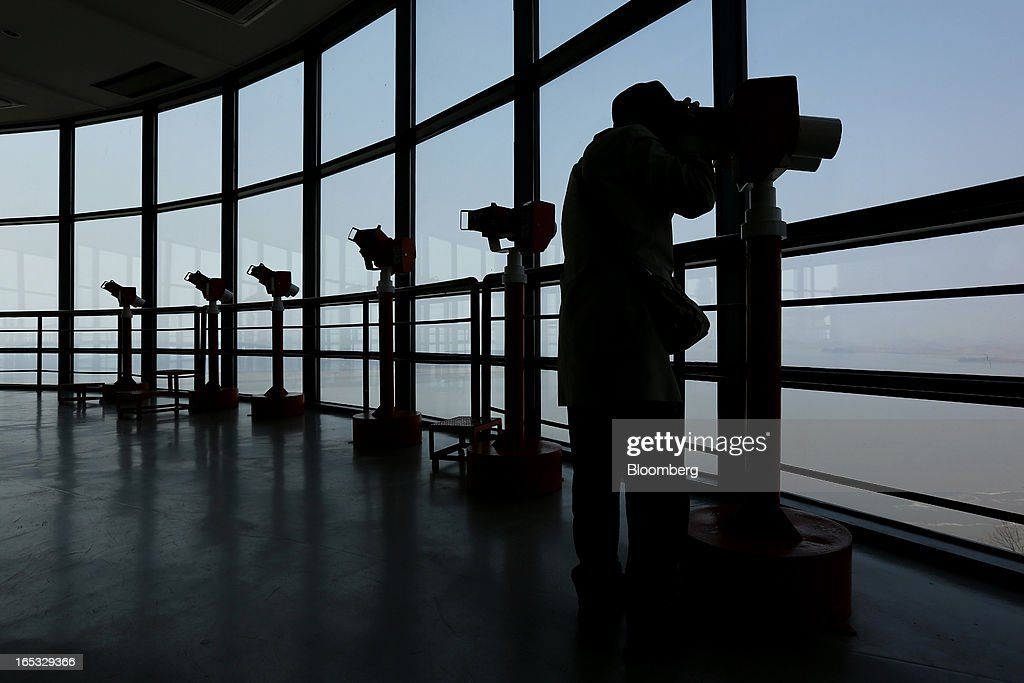 A visitor uses binoculars to look towards the North Korean village of Gaepung-Gun at the Odusan Unification Observatory near the demilitarized zone (DMZ) in Paju, South Korea, on Wednesday, April 3, 2013 North Korea prevented South Korean workers from entering a jointly run industrial park today, adding to tensions after saying it will restart a mothballed nuclear plant and threatening to attack its southern neighbor. Photographer: SeongJoon Cho/Bloomberg via Getty Images