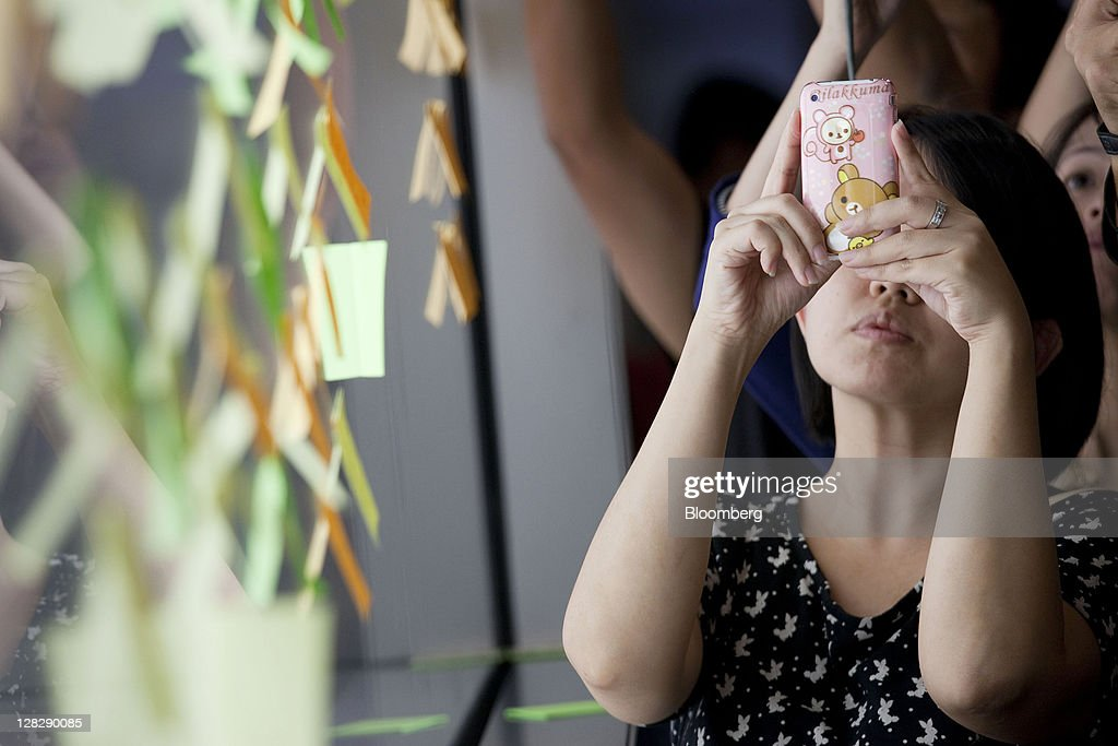 A visitor uses her Apple Inc. iPhone to photograph messages left in tribute to Steve Jobs, co-founder and former chief executive officer of Apple Inc., attached to a window of the Apple Inc. store in Hong Kong, China, on Thursday, Oct. 6, 2011. Jobs who built the world's most valuable technology company by creating devices that changed how people use electronics and revolutionized the computer, music and mobile-phone industries, died on Oct. 5. Photographer: Jerome Favre/Bloomberg via Getty Images