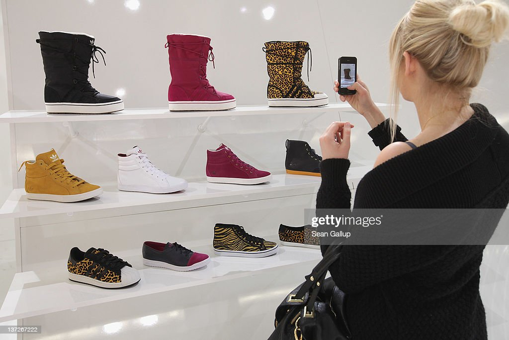 A visitor uses her smartphone to photograph shoes that are part of the adidas Originals Fall/Winter 2012 collection at the adidas Originals stand at the Bread and Butter 2012 fashion trade fair on January 18, 2012 in Berlin, Germany.