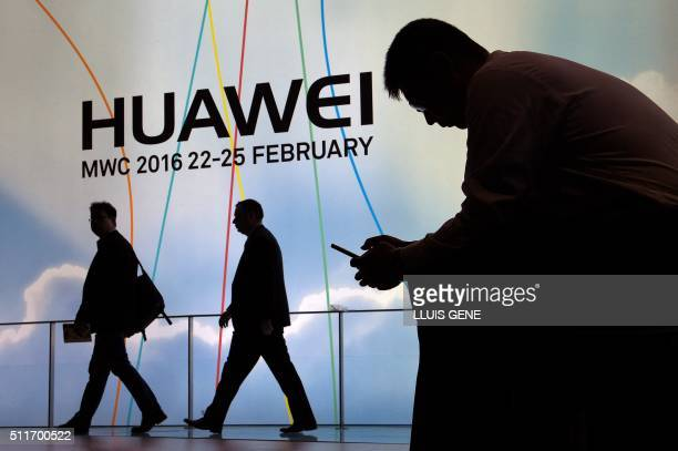 A visitor uses his mobile phone next to the stand of Chinese multinational networking and telecommunications equipment and services company Huawei on...