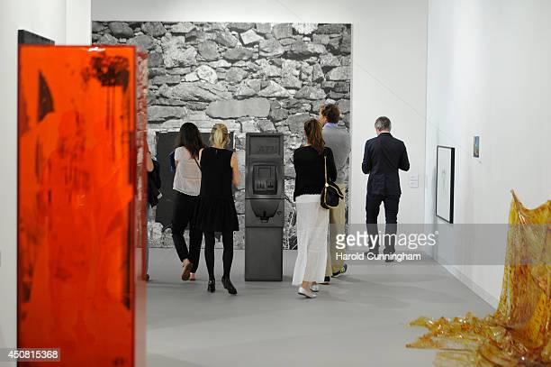 Visitor view artworks in The Modern Institute gallery of Art Basel on June 18 2014 in Basel Switzerland Art Basel one of the most prestigious art...