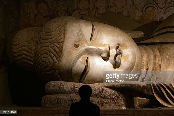 A visitor views a replica of Buddhist statue from the Mogao Cave during the Dunhuang Art Exhibition at the National Art Museum of China on January 21...