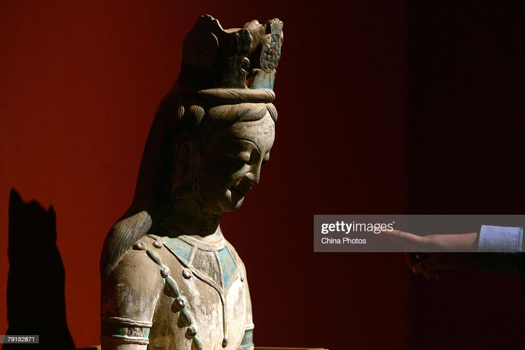 A visitor views a replica of Guanyin Bodhisattva statue during the Dunhuang Art Exhibition at the National Art Museum of China on January 21 2008 in...