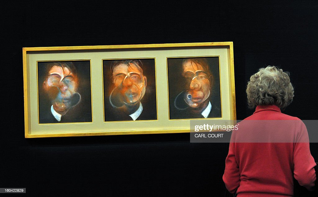 A visitor views a triptych painting entitled 'Three Studies for a Self-Portrait' by British artist Francis Bacon at Sotheby's auction house in central London on January 31, 2013. Due to form part of the Contemporary Art Evening Sale on February 12, it is expected to fetch between 10-15 million GBP (12-18 million EUR - 16-24 million USD).