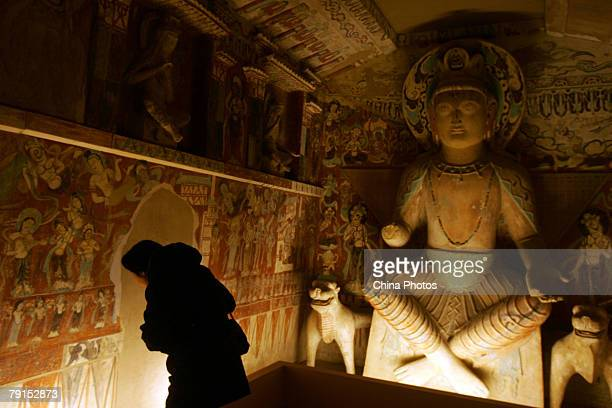 A visitor views replica of parts of the Mogao Cave during the Dunhuang Art Exhibition at the National Art Museum of China on January 21 2008 in...