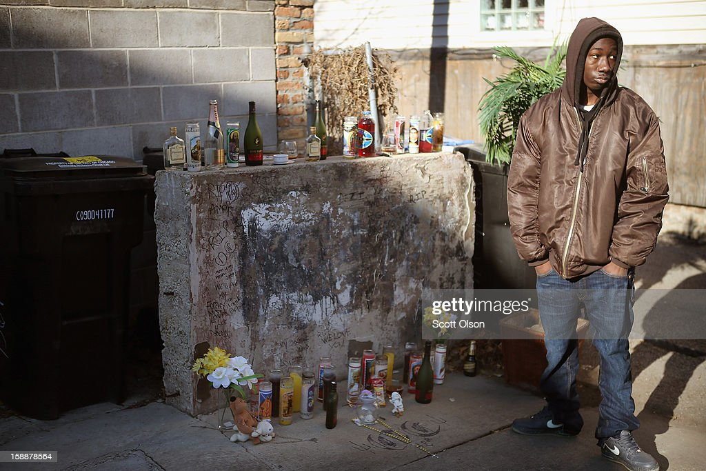 A visitor views the small memorial which marks the spot in an alley where 20-year-old Octavius Dontrell Lamb was shot yesterday and killed, on January 2, 2013 in Chicago, Illinois. At 3:45 a.m., less than four hours into the new year, Lamb became the first murder victim of 2013 in Chicago, a city which saw more that 500 murders in 2012. Fifteen people were shot in Chicago on the first day of the year, three fatally. Aurora, Illinois' second largest city, had no murders in 2012.