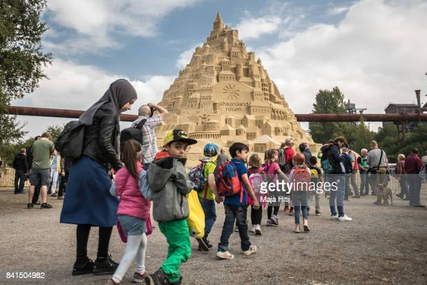 Visitor walk near the Sandburg sandcastle on September 1 2017 in Duisburg Germany A local travel agency commissioned the building of the sandcastle...
