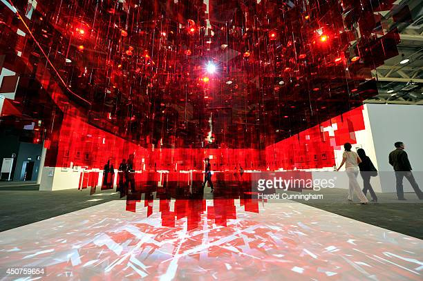 Visitor walk next to the artwork 'Continuel Mobile Sphere rouge' by Michelangelo Pistoletto in the Unlimited section of Art Basel on June 17 2014 in...