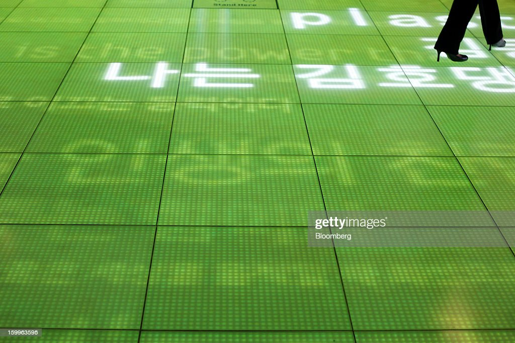 A visitor walks across the Message Floor at the Samsung Electronics Co. Samsung d'light showroom and store in Seoul, South Korea, on Wednesday, Jan. 23, 2013. Samsung, in a preliminary statement of results on Jan. 8, reported an 89 percent jump in profit in the three months ended in December, boosted by its Galaxy line of smartphones. Photographer: Woohae Cho/Bloomberg via Getty Images