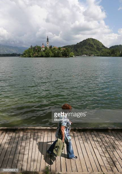 A visitor walks along a pontoon on the shore of Lake Bled beyond the church of the Assumption of Mary a pilgrimage site and tourist attraction in...