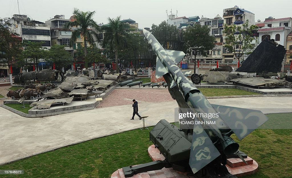 A visitor walks between a Soviet-made SAM-2 missile (C) and wreckage of a downed US bombarder B-52 on display at the museum 'Victory over B.52s' in Hanoi on December 7, 2012. Vietnam has been launching celebrations marking the 40th anniversary of 'Dien Bien Phu in the air' recalling Hanoi's battle against US massive bombing campaign carried out by the US Airforce strategic bombarders B-52 in December 1972. Vietnamese Northern forces have claimed downing at that time some thirty four B-52 aircrafts. As parts of a propaganda programme on the event, Hanoi has organised workshops and exhibitions. AFP PHOTO/HOANG DINH Nam