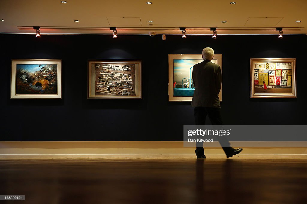 A visitor walks in front of a pieces of work by Australian artists at Bonhams auction house on May 7, 2013 in London, England. The Australian Art sale will be held at Bonhams in Sydney on June 26, 2013. The collection, which has never been seen before in public belongs to Neighbours producer Reg Grundy.