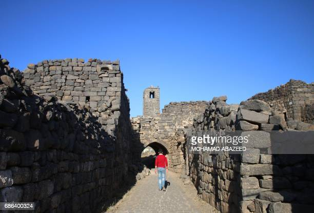 A visitor walks in the ancient city of Bosra alSham which is listed as a UNESCO World heritage site in the southern Syrian province of Daraa on May...