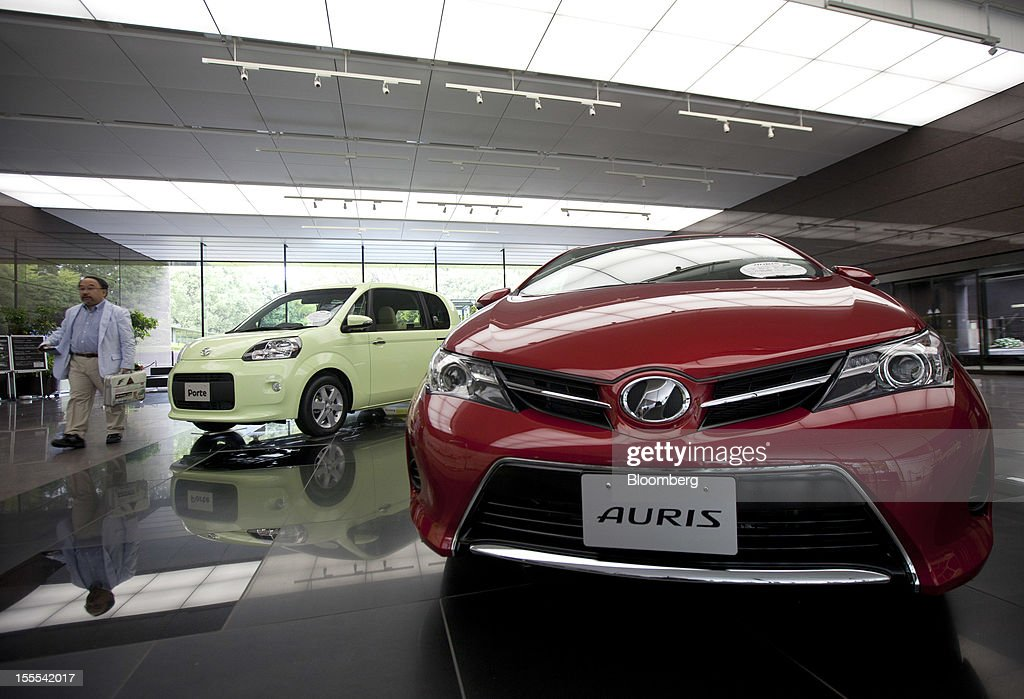 A visitor walks near a Toyota Motor Corp. Auris compact vehicle, right, displayed at the company's head offices in Tokyo, Japan, on Monday, Nov. 5, 2012. Toyota Motor Corp., Asia's biggest carmaker, raised its full-year profit forecast as rising demand for the Prius hybrid in the U.S. and Japan helped make up for slumping sales in China. Photographer: Tomohiro Ohsumi/Bloomberg via Getty Images