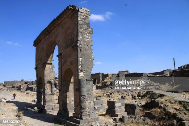 A visitor walks near the Door of Victory in the ancient city of Bosra alSham which is listed as a UNESCO World heritage site in the southern Syrian...