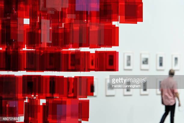 A visitor walks next to the artwork 'Continuel Mobile Sphere rouge' by Michelangelo Pistoletto in the Unlimited section of Art Basel on June 16 2014...