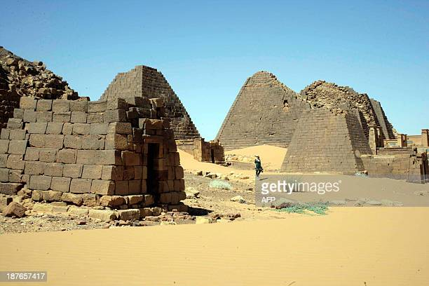 A visitor walks on November 10 2013 past pyramids in the cemetary of Meroe north of Khartoum Sudan The Meroe dynasty the last in a line of 'black...