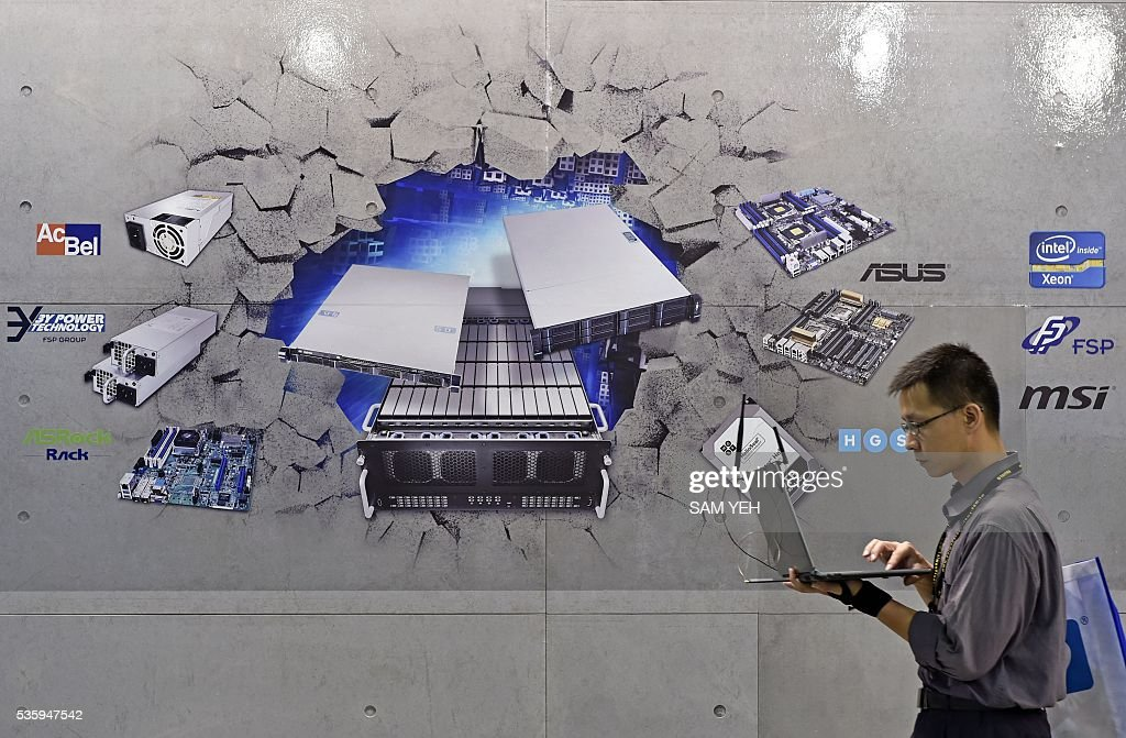 A visitor walks pass a wall painted with various information technology products the annual Computex computer exhibition in Taipei on May 31, 2016. More then 5,000 booths from thirty countries take part in COMPUTEX Show between May 31 to June 4. / AFP / SAM YEH