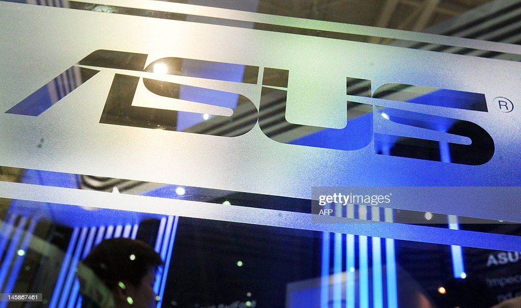 A visitor walks past a ASUS logo during the 2012 Computex in Taipei on June 7, 2012. Computex is Asia's leading IT trade fair. AFP PHOTO / Mandy CHENG