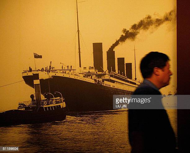 A visitor walks past a big portrait of the Titanic at the Titanic Experience and Priceless Artifact Exhibition in Shanghai 11 August 2004 The Titanic...