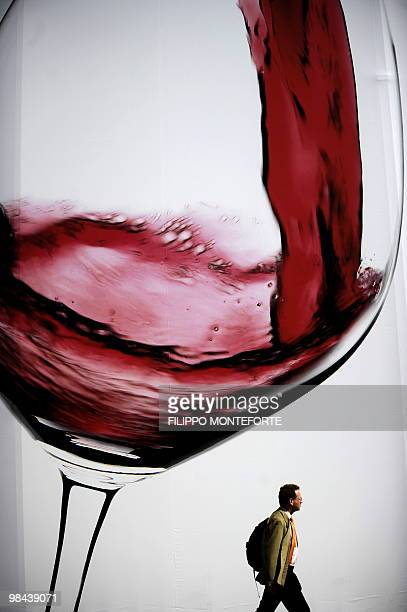 A visitor walks past a giant placard showing a glass of wine on the first day of the 44th Vinitaly wine fair in Verona on April 8 2010 150 000...