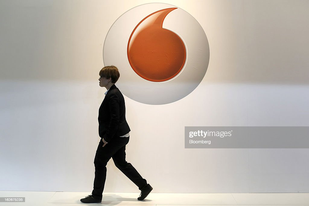 A visitor walks past a logo outside the Vodafone Group Plc pavilion at the Mobile World Congress in Barcelona, Spain, on Monday, Feb. 25, 2013. The Mobile World Congress, where 1,500 exhibitors converge to discuss the future of wireless communication, is a global showcase for the mobile technology industry and runs from Feb. 25 through Feb. 28. Photographer: Simon Dawson/Bloomberg via Getty Images