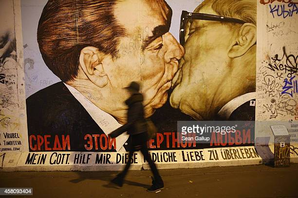 A visitor walks past a mural showing former Soviet leader Leonid Brezhnev kissing former East German communist leader Erich Honecker by Russian...