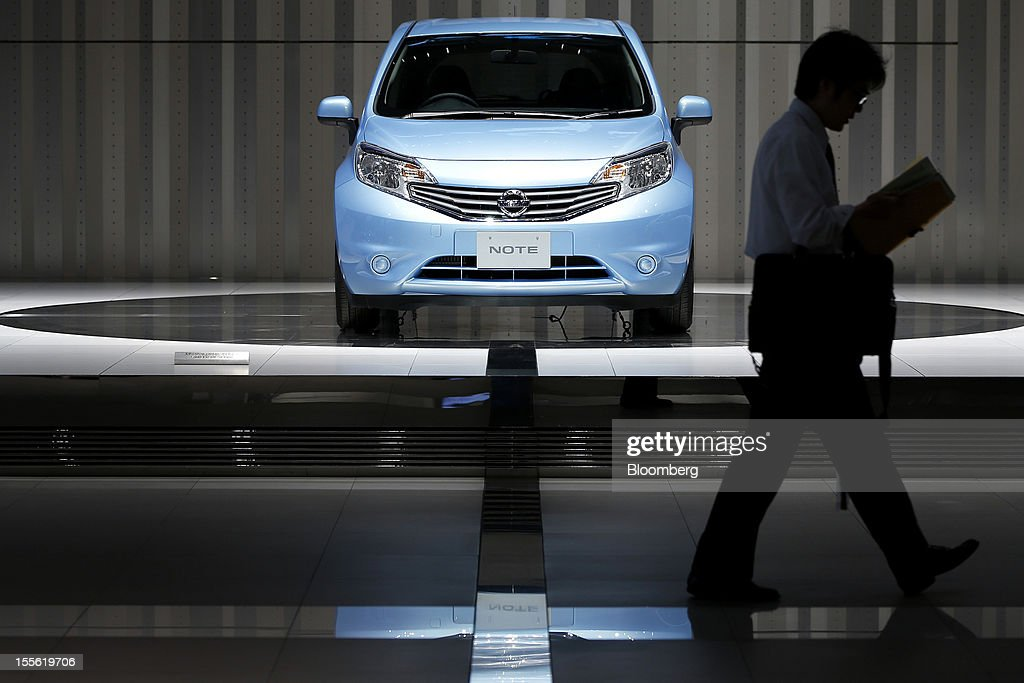 A visitor walks past a Nissan Motor Co. Note vehicle displayed at the company's headquarters in Yokohama City, Kanagawa Prefecture, Japan, on Tuesday, Nov. 6, 2012. Nissan, the top Japanese seller of vehicles in China, cut its full-year net income forecast 20 percent after consumer backlash stemming from a territorial dispute sent sales lower in its largest market. Photographer: Kiyoshi Ota/Bloomberg via Getty Images