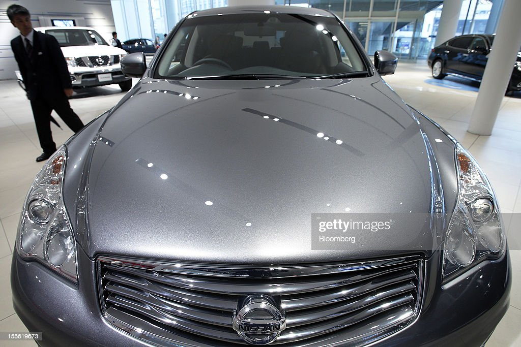 A visitor walks past a Nissan Motor Co. Skyline Crossover vehicle displayed at the company's headquarters in Yokohama City, Kanagawa Prefecture, Japan, on Tuesday, Nov. 6, 2012. Nissan, the top Japanese seller of vehicles in China, cut its full-year net income forecast 20 percent after consumer backlash stemming from a territorial dispute sent sales lower in its largest market. Photographer: Kiyoshi Ota/Bloomberg via Getty Images