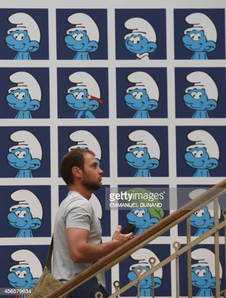 A visitor walks past a panel exhibiting characters from the Belgian comic series 'The Smurfs' created by Belgian cartoonist Peyo in the 'Centre Belge...