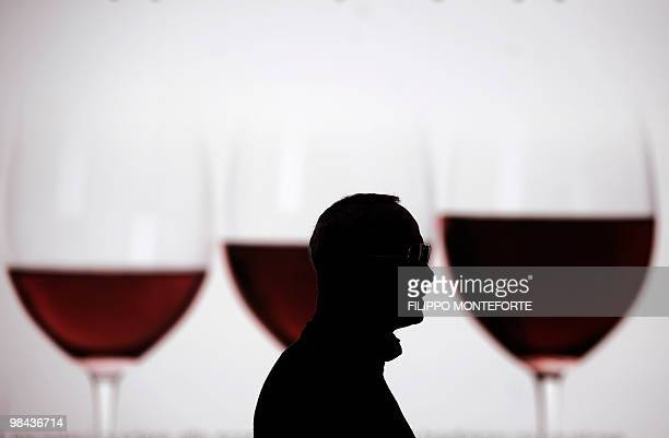 A visitor walks past a picture showing three glasses of wine on the first day of the 44th Vinitaly wine fair in Verona on April 8 2010 150000...