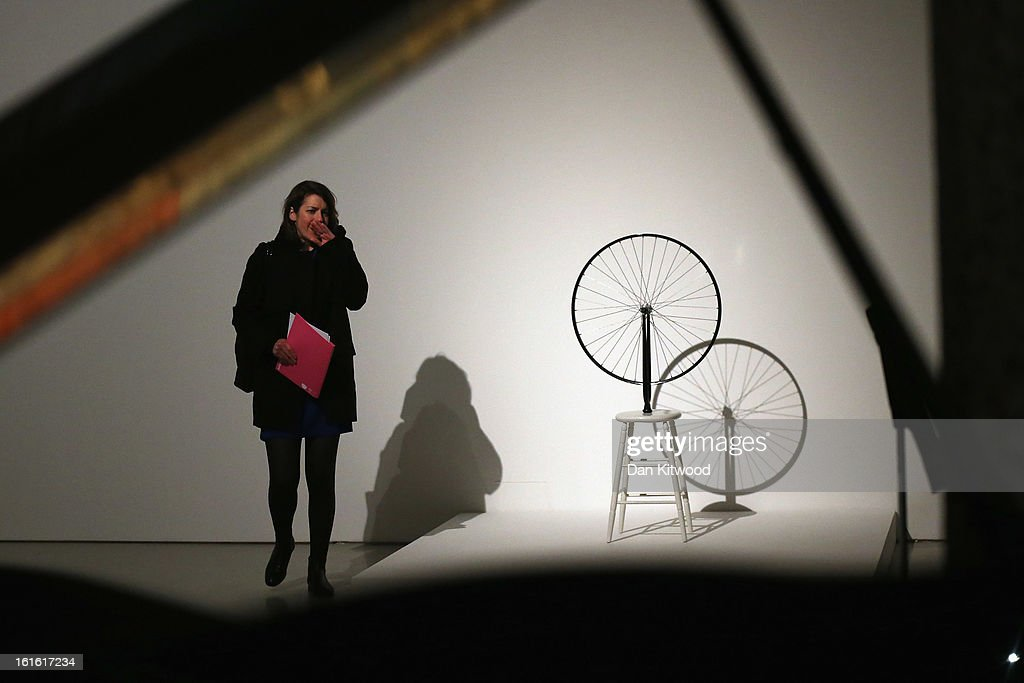 A visitor walks past a piece of work by Marcel Duchamp entitled 'Bicycle Wheel' during a press preview of 'The Bride and the Bachelors' exhibition at the Barbican Art Gallery on February 13, 2013 in London, England. The piece makes up a selection of works by artists and choreographers including Marcel Duchamp, Merce Cunningham, John Cage, Robert Rauschenberg and Jasper Johns, and runs at the Barbican Art Gallery until June 9, 2013.